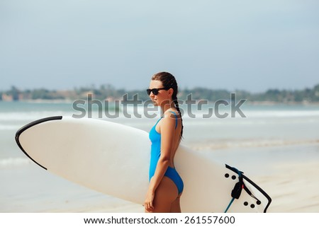 attractive young woman in blue bikini  holding surfboard on sandy beach