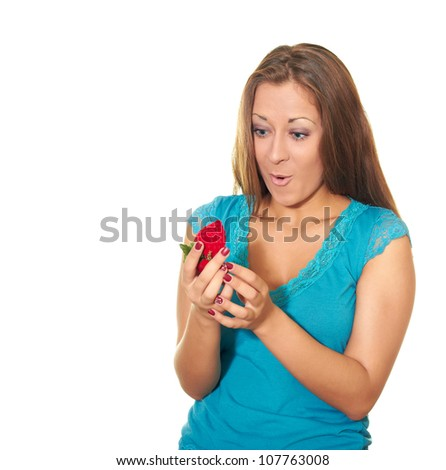 Attractive young woman  in blue blouse opens a present and is surprised by an engagement ring isolated on a white background