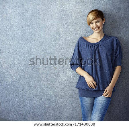 Attractive young woman in blue jeans leaning against wall, smiling - stock photo