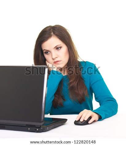 Attractive young woman in blue shirt working on laptop and stares at the laptop screen. Isolated on white background