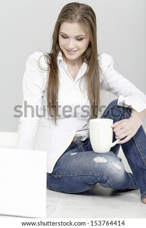 Attractive young woman in casual clothes on her laptop at home
