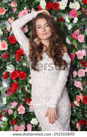 Attractive young woman in classy white dress on flower wall background - stock photo