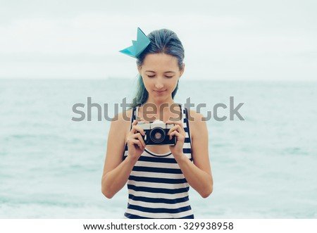 Attractive young woman in costume of sailor and origami ship in hairstyle standing with old photo camera on background of sea in summer - stock photo