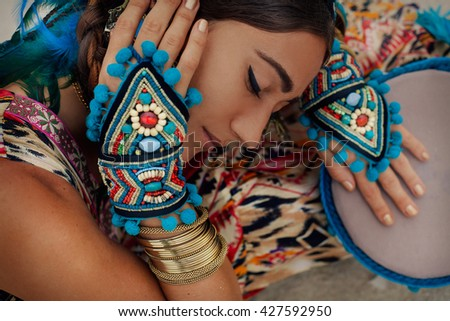 attractive young woman in ethnic jewelry with drum. close up portrait.  - stock photo
