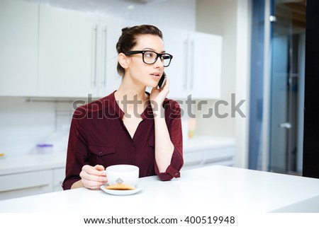 Attractive young woman in glasses drinking tea and using smartphone on the kitchen - stock photo