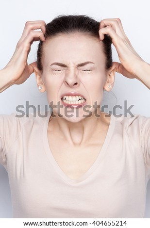 Attractive young woman in great anger. She is furious, she was crying and screaming loudly. She feels hard pain. Strong emotions, anger, rage, despair, anger, hatred. Facial expressions. - stock photo