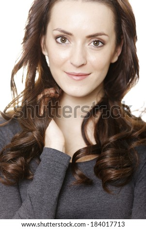 Attractive young woman in grey jumper smiling isolated on white background.
