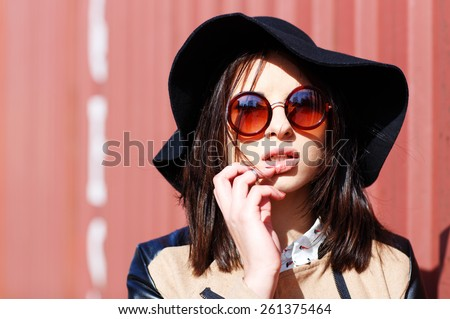 Attractive young woman in hat outdoors - stock photo