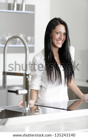 Attractive young woman in her elegant kitchen - stock photo