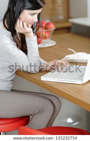 Attractive young woman in her elegant kitchen taking a break with her laptop - stock photo