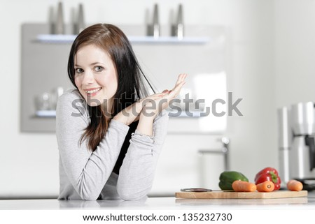 Attractive young woman in her elegant kitchen with fresh vegetables ready to cook. - stock photo