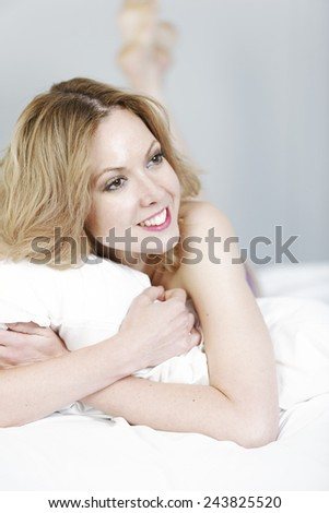 Attractive young woman in her underwear lying on a bed - stock photo