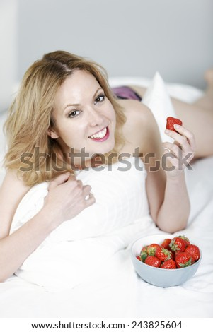 Attractive young woman in her underwear lying on her bed eating fresh strawberries - stock photo