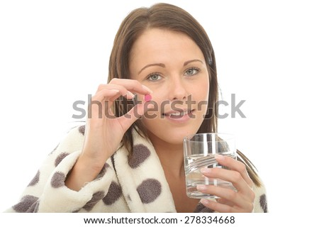 Attractive Young Woman In Her Warm Cosy Dressing Gown Feeling Poorly and Unwell Taking Medicine - stock photo