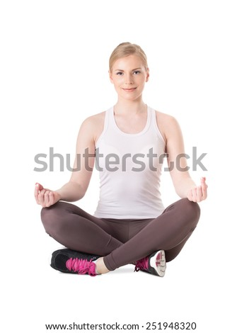 Attractive young woman in lotus position. Young woman practicing yoga. - stock photo