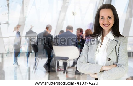Attractive young woman in office against of glass reflection and business meeting going at the background - stock photo