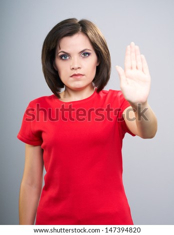 Attractive young woman in red shirt showing a stop sign. Isolated on a gray background - stock photo