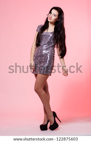 Attractive young woman in short dress on pink background