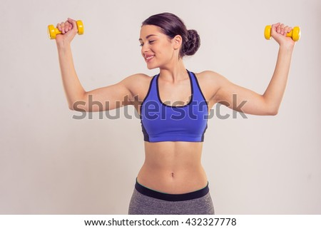 Attractive young woman in sportswear is holding dumbbells, looking at her muscles and smiling, on a gray background - stock photo