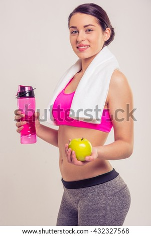 Attractive young woman in sportswear with a towel on her neck is smiling, holding a bottle of water and an apple, on a gray background - stock photo