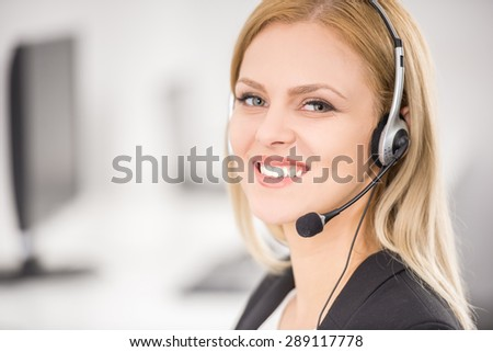Attractive young woman in suit sitting at call center office and working. - stock photo