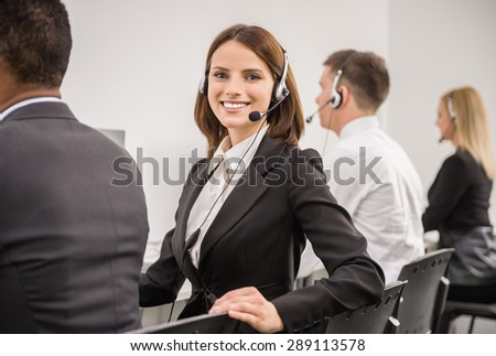 Attractive young woman in suit sitting at call center office with colleagues and working. - stock photo