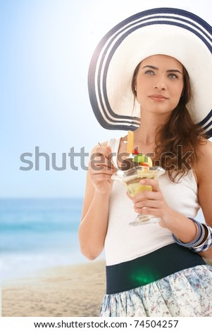 Attractive young woman in summer straw eating icecream on beach, looking away, smiling.? - stock photo