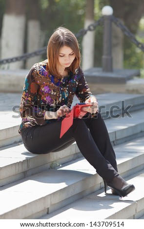 Attractive young woman in the park. Girl uses touchpad on open air - stock photo