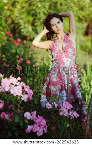 Attractive young woman in the rose garden