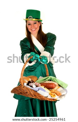 Attractive young woman in traditional St Patrick holiday outfit, food basket with cheese, bread, beer and meat in front. Studio shot.