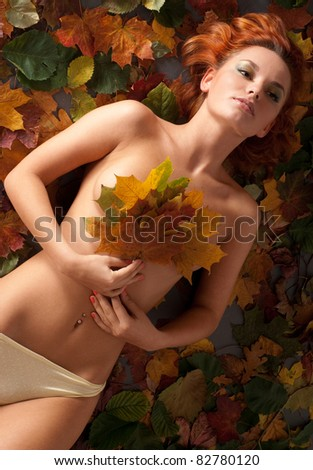 Attractive young woman in underwear over autumn leaves - stock photo