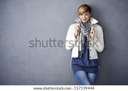 Attractive young woman in white jacket and scarf standing by grey wall - stock photo