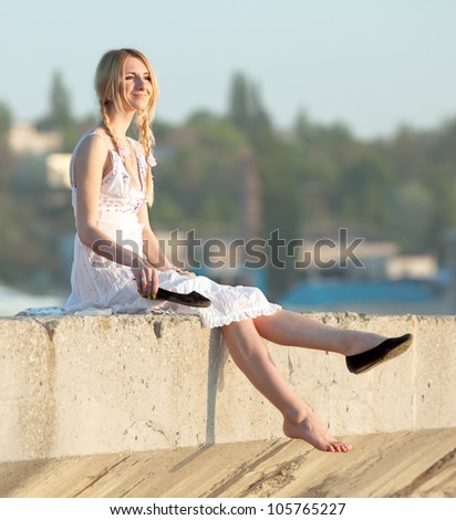 Attractive young woman in white sundress puts on shoes on open air. Girl with pigtails puts on shoes looks away smiling