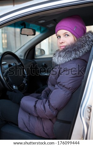 Attractive young woman in winter clothes sitting in car - stock photo
