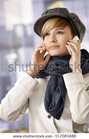 Attractive young woman in winter clothes, talking on mobile phone - stock photo