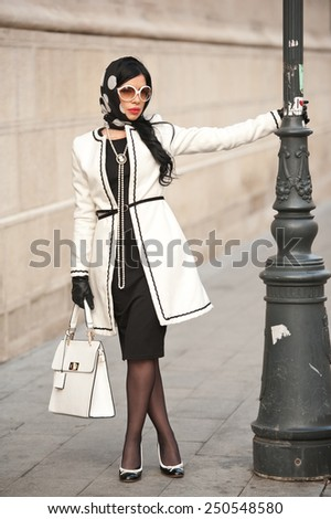 Attractive young woman in winter fashion shot. Beautiful fashionable young girl in black and white outfit posing on avenue. Elegant brunette with headscarf, sunglasses and handbag in urban scenery.  - stock photo