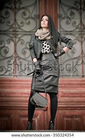 Attractive young woman in winter fashion shot with wrought iron decorated doors in background. Beautiful fashionable female - black leather outfit. Elegant long hair brunette posing in urban scenery. - stock photo