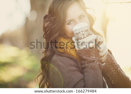 Attractive young woman in wintertime outdoor on sunset background - stock photo