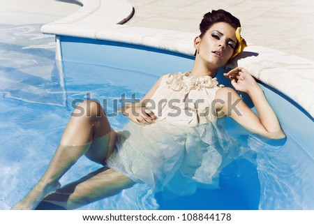 Attractive young woman inside a swimming pool, wearing a dress