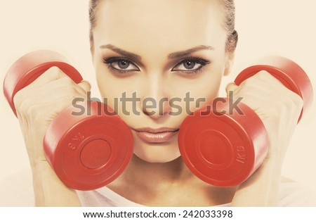 Attractive young woman is engaged in exercises with dumbbells. Authors color and added grain  - stock photo