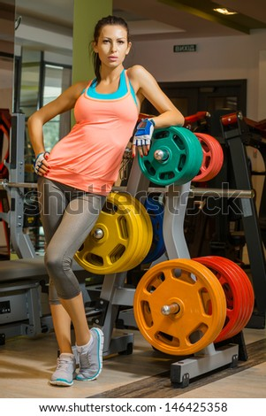 attractive young woman is engaged in fitness sport club - stock photo
