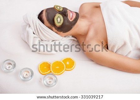 Attractive young woman is lying with chocolate mask on her face at spa. She is relaxing and smiling. The girl is wearing white towel. Pieces of kiwi on her eyes