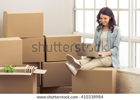 Attractive young woman is moving, sitting among cardboard boxes, using a laptop and smiling - stock photo