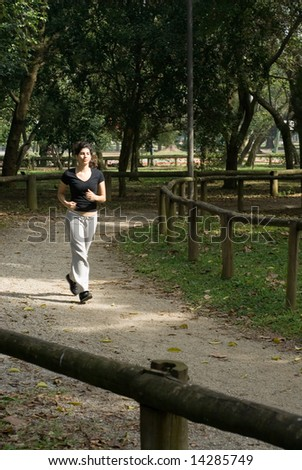 Attractive, young woman is running through the park on the joggers path.  Vertically framed shot. - stock photo