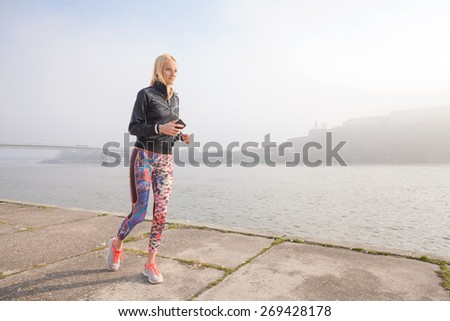 Attractive young woman jogging by the river early in the morning - stock photo
