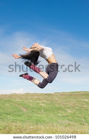 Attractive young woman jumping on open air. Brunette jumps on background of sky - stock photo