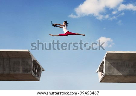 Attractive young woman jumping with laptop over concrete bridge