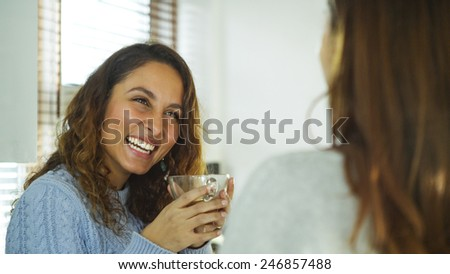 Attractive young woman laughing whilst talking to her friend - stock photo