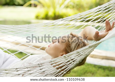 Attractive young woman laying down and relaxing on a white hammock while on vacation in a tropical garden. - stock photo