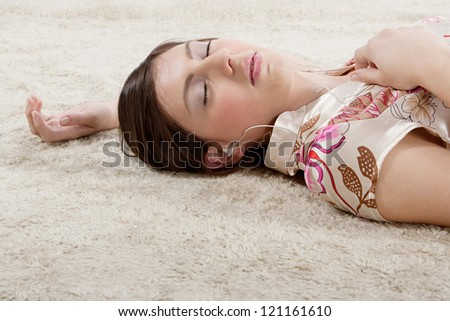 Attractive young woman laying down on a furry carpet at home, listening to music with her earphones, relaxing with her eyes closed. - stock photo
